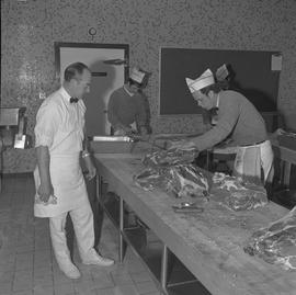 Meat cutting, 1968;  an instructor watching a student cut meat ; two students in background