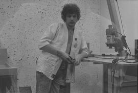 Student wearing an unbuttoned shirt leaning on a desk for a microscope; picture is being taken th...