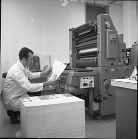 BCVS Graphic arts ; a man next to and printing press and looking at printed material