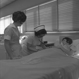 Practical nursing, Prince George, 1968; instructor checking a patient's pulse and a student obser...
