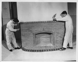 Bricklaying; two students building a brick fireplace - one student tapping a brick on the mantel ...