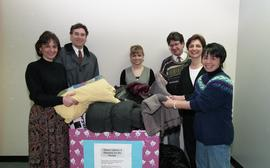 "Staff members with a box labeled ""Warm clothes and blankets for the needy"" [1 of 5 phot..."