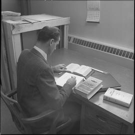 Stationary engineering, 1968; man sitting at a desk taking notes from an engineering textbook ; s...