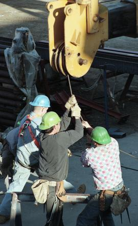 Ironwork, students wearing tool belts, hard hats and uniforms while using the tip a crane (?) [3 ...