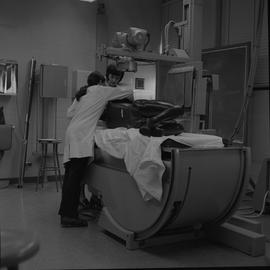 Medical radiography, 1968; two women in lab coats adjusting a manikin laying on the table of an x...
