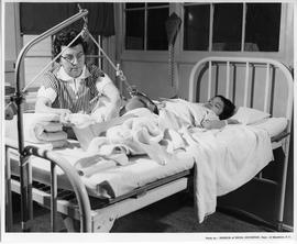 Nurse with child patient, leg supported (ca. 1963)