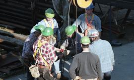 Ironwork, students wearing tool belts, hard hats and uniforms while using the tip a crane (?) [7 ...