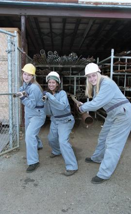 BCIT women in trades; plumbing, students in uniforms and hard hats carrying piping material [3 of...