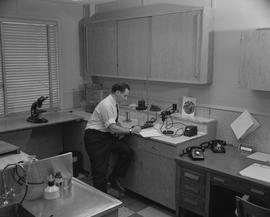 Forest Products, 1964; a man sitting at a desk in a testing lab and writing in a notebook ; wood ...