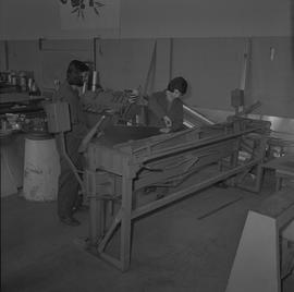 Sheet metal, 1968; two students using a large piece of machinery ; workshop in background