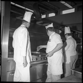 BC Vocational School Cook Training Course ; a student putting meat on a grill while instructor su...