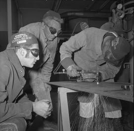 Welding, Terrace, 1968; two men watching another man welding a sheet of metal
