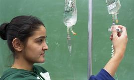 General Nursing, student checking intravenous drip bag [2 of 5 photographs]