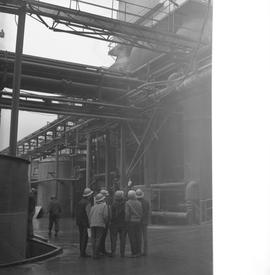 Forestry, Wood fiber BCIT tour, November 26, 1965; a group of men wearing hard hats standing outs...