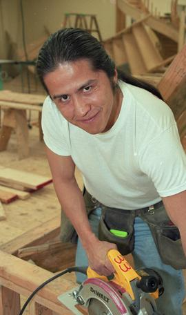 First Nations student wearing a tool belt and using a woodworking tool [8 of 13 photographs]