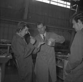 Sheet metal, 1968; instructor holding a circular piece of metal and talking to two students ; wor...