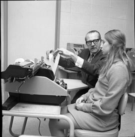 BC Vocational School Commercial Program; instructor showing a student a typing book