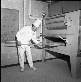 BC Vocational School Baking Course ; instructor Bert J. Phillips using a peel to remove bread fro...