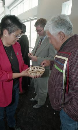 First Nations (?) woman presenting a wooden bowl filled with stones to a First Nations elder [2 o...