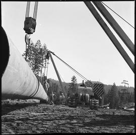 Heavy duty equipment operator, Nanaimo ; pipelayers moving a large pipe ; two men watching