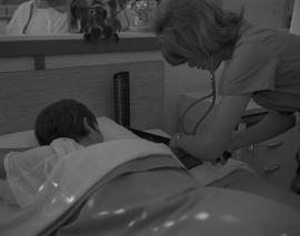 Practical nursing, 1968; female nurse attending to a patient
