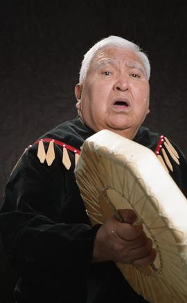 Bob George, First Nations elder, in First Nations garment playing an instrument [17 of 36 photogr...