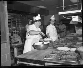 BC Vocational School Cook Training Course ; student icing a cake as another student observes ; a ...