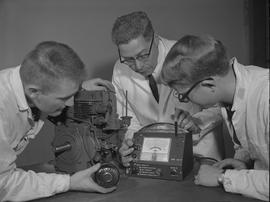 Mechanical maintenance, 1968; an instructor and two students using a measuring device on a motor ...