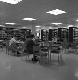 BCIT Burnaby campus library ; people sitting at desks ; library stacks [2 of 3]