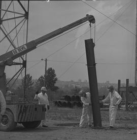 Structural steel, 1968; workers using a crane to place a large piece of steel into the ground [2 ...