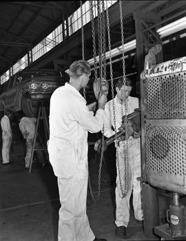 BCVS Heavy duty mechanic program ; a student holding an engine piece, a student holding chains fr...