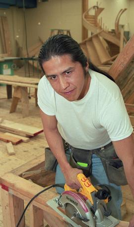 First Nations student wearing a tool belt and using a woodworking tool [12 of 13 photographs]