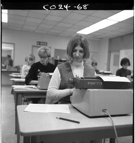 B.C. Vocational School; Commercial Program students sitting at electric typewriters in a classroo...