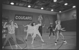 Staff (?) in costumes doing aerobics in a gymnasium [13 of 15 photographs]