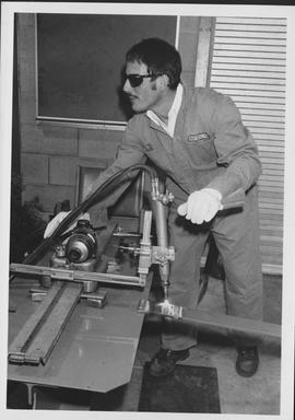 Man wearing sunglasses, using equipment in NE08