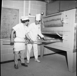BC Vocational School Baking Course ; student using a peel to remove bread from an oven ; instruct...