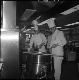 BC Vocational School Cook Training Course ; instructor looking in a large pot and student observing