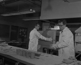 Mining, 1966; a man in a lab coat moving a hot cup to a table ; man in a lab coat working in back...
