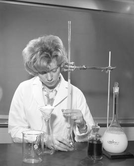 Medical Lab; a woman in a lab coat titrating liquid