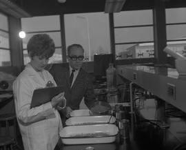 Food Processing Technology, 1966; woman wearing a lab coat writing notes on a clip board ; instru...