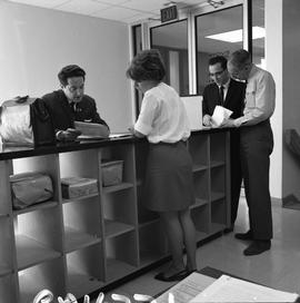 BCVS Graphic arts ; four people standing at a shelf and looking at papers [2 of 3]