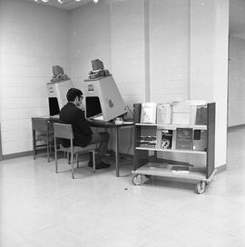 BCIT Burnaby campus library ; man looking at a microfilm reader ; a cart of books