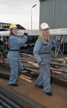 BCIT women in trades; plumbing, students in uniforms and hard hats carrying piping material [9 of...