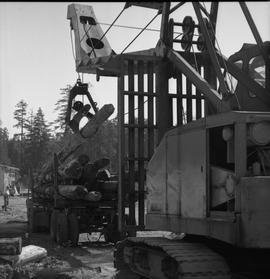 Logging, 1969; a log loader lifting a log onto a trailer