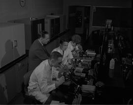 Food Processing Technology, 1966; three students in lab coats using microscopes, instructor talki...