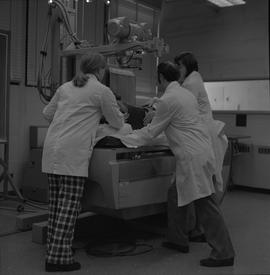 Medical radiography, 1968; three people in lab coats moving a manikin on the table of an x-ray ge...