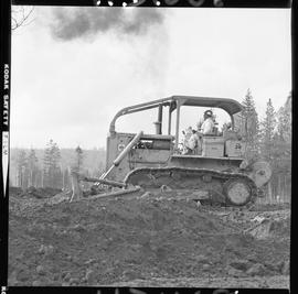 Heavy duty equipment operator, Nanaimo ; side view of a man operating a bulldozer moving dirt