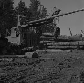 Logging Loading, Nanaimo, 1968; a log lifter moving logs ; two large piles of logs