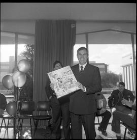 Merger of BCIT and PVI celebrations April 1986; Roy Murray holding up commemorative comic [3 of 3...