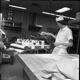 BC Vocational School Cook Training Course ; student putting dough into a machine the flattens the...